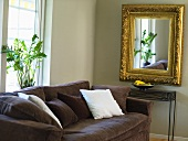 A brown upholstered sofa and a mirror with a gold frame in a the corner of a living room
