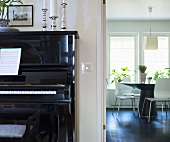 Piano and a view into a dining room with designer furniture