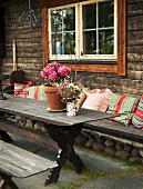 A rustic wooden table with colourful cushions against a wooden house facade
