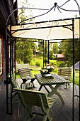 Garden furniture on a wooden terrace under a canopy with a metal frame
