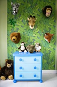 A child's room - a blue chest of drawers in front of a wall with painted jungle design and hung with plush animal heads