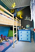 A child's bedroom with a bunk bed and a blue chest of drawers in front of a dark blue wall