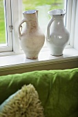 White ceramic jugs on a window sill