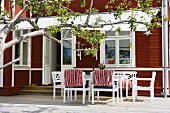 White patio furniture under a marquee in front of a red brown wooden facade