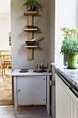 A children's kitchen and a homemade wooden shelf in the corner