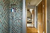 A tiled shower with taps and view through an open door into a living room