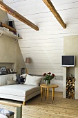 A bed and a side table under a slopping roof with white wood panelling and a TV mounted on the wall above a stack of wood in a niche in the wall