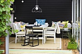 Cozy winter garden with white patio furniture in front of a black wall