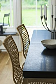 Wicker chairs and candelabra on a table in front of a French window