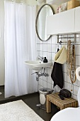 Sink with mirror on a white tile wall and shower curtain