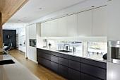 Offene Designerküche - schwarze und weisse Einbauschränke vor Fensterband