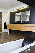 A designer bathroom - a sunken bath and a built-in washstand with a mirror on a black wall and indirect lighting
