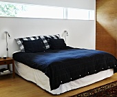 A double bed with black bedclothes and strip lighting on the wall