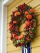 A wreath of lampion flowers and rosehips hanging on a door