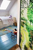A child's bedroom with a blue-painted wooden floor, a bed under a skylight window and a door decorated with a photo of a garden