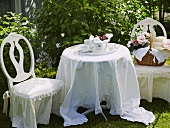 A festively laid table set with tea and a basket on a covered chair in a garden