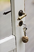 A glass door with a white frame and a metal handles with bunch of keys in the lock