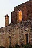 Steinfassade einer romanischen Burg im Abendlicht