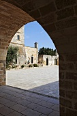 View through an archway of a stone piazza and historic buildings