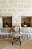 Wall niches with cacti in a stone wall and upholstered rattan chair