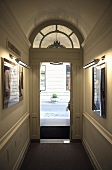 Hallway with an open front door with a fanlight with a view onto a street