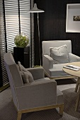 Armchairs upholstered in gray in the corner of a living room with a closed Venetian blind with ambient lighting