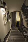 Stairway with ambient wall lighting with a stair runner and metal handrail