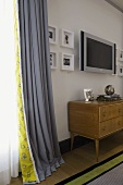 1950's wooden chest of drawers and flat screen TV in front of a wall next to gray curtains