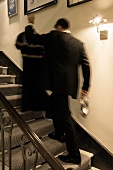Person with clothes on a hanger in his hand running up stairs