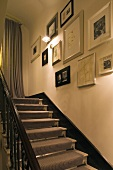 Stairway with ambient wall lighting with a striped stair runner and collection of pictures on the wall