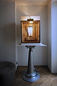 Miniature model of a bathroom on an adjustable display stand in a window niche