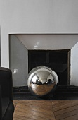 Stainless steel ball on a wood floor laid with a herringbone pattern in front of a fireplace