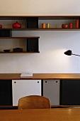 Sideboard und Wandregal beleuchtet vor Tischlampe