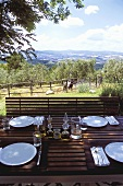 Set table on a terrace with a view of the Mediterranean countryside