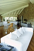 White sofa under a beam ceiling and natural stone wall in the living room of a country home