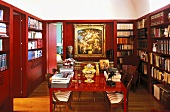 Red lacquered table in a library with red paneled walls and built in book shelves