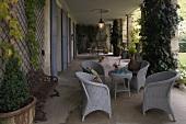 Hellgraue Korbmöbel und Pflanzenkübel in Loggia einer Villa mit Gartenblick