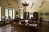 Elegant living room in an old villa with vaulted ceiling and a living room suite covered in red velvet