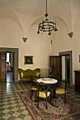 Vaulted ceiling in the salon of a villa with antique furniture on a floor with checkerboard pattern and a view of an open door