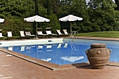 Clay planter beside a pool and lounge chairs with a sun umbrella reflected in the water