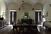 Vaulted ceiling in the darkened dining room of a villa with period furniture and windows with shutters