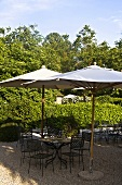 Sunny day -- garden chairs and table with a sun umbrella on a gravel patio
