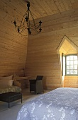 Bedroom in an attic with bright wood paneling on the walls and ceiling