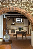 View through a brick archway into the kitchen of a country home with a dining area