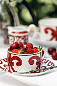 Patterned tea cup with red berries and cherries