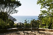 Terrace with black rattan chairs and a view of the sea