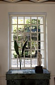 Palm fronds in a vase and stone statue in front of a mullioned window with a view of the garden