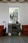 Eingebauter Kamin unter Sprossenfenster mit muschelförmigen Bodenleuchten