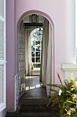 Villa with a pink facade and a view through an archway of a floor to ceiling window