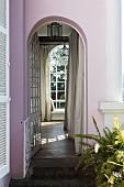 Villa mit rosafarbener Fassade und Blick durch Rundbogen auf raumhohes Fenster
